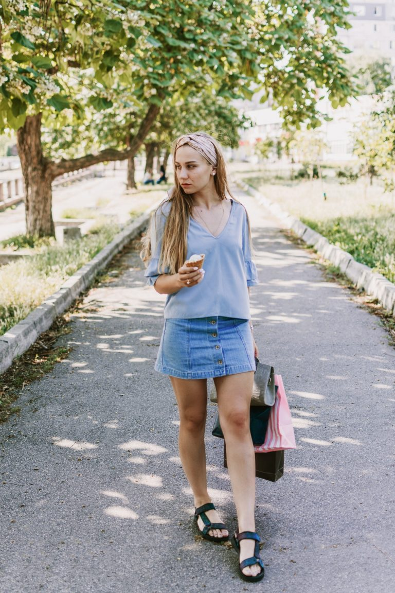 Summer city lifestyle girl portrait. Stylish young woman with ice cream in a waffle cone in her hand